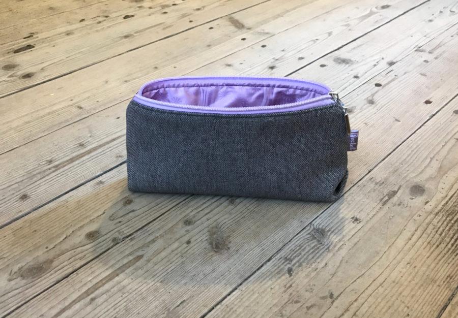 Kosmetická taštička oděruodolná šedá s fialkovým zipem